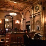 High ceilings, low lights, lots of gold and warm tones, a piano player plays music for the patrons of the bar.
